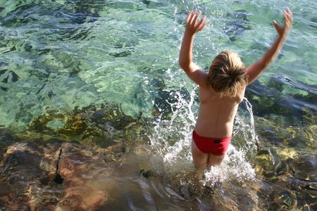 zest for life: Zest for Life:  Boy splashes water overhead from an ocean rockpool.