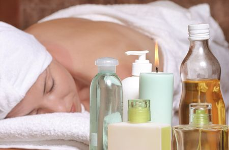 Woman on massage table with oils, essential oils, candles, scents.  Focus on products. Stock Photo