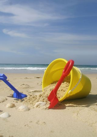 A childs yellow beach bucket and spades.    Primary colors red yellow blue