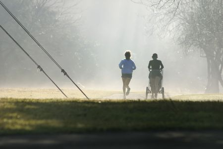 despite: Two joggers one with a  stroller exercise despite the misty fog. Stock Photo