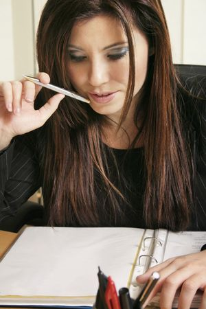 assignment: Woman reveiws a - document, - assignment, - resume, - tender.... etc.   (Blank to protect owners copyright). Stock Photo