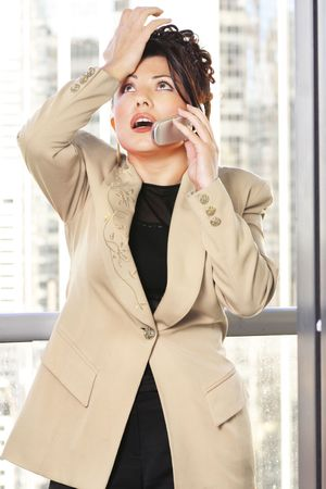 Businesswoman makes a gesture while on the phone. -- eg: annoyed, frustrated, forgetful, mistake