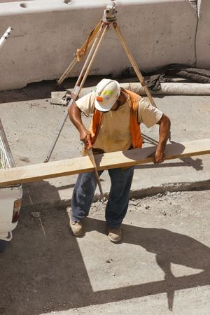 Builder saws a plank of wood.  Builders survey tripod in the background. Stock Photo