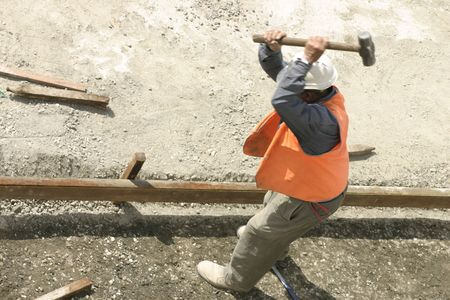 pounding head: Workman swings a mallet high above his head pounding stakes into hard ground..    Motion blur in his upper area