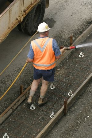 A worker using a hose  Some motion in one foot.