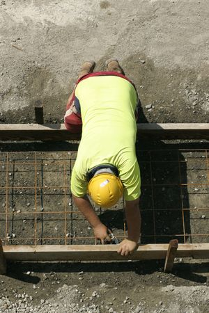 buiding: A worker laying securing mesh before cementing