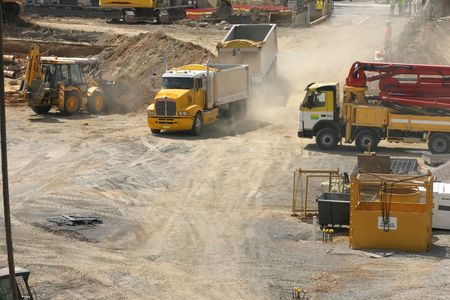 buiding: A truck rumbles into a construction site.  An earthmover scoops up a laod of dirt and there are workmen in discussion.