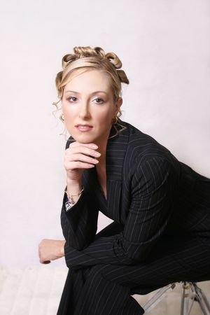 Glamorous woman in a pinstripe suit sitting on a stool.  This photo could be used for fashion, business, beauty Business Fashion -  photo request