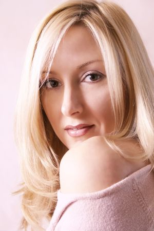 coy: Casual Look - Young woman glances toward the viewer. Blonde tendrils curling about her face. She is wearing an off the shoulder jumper exposing her shoulder Stock Photo