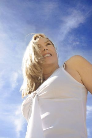 congenial: A young woman with windswept hair has an optimistic outlook.  Angled view against pretty windswept clouds.