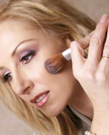 beautify: A woman touches up her makeup