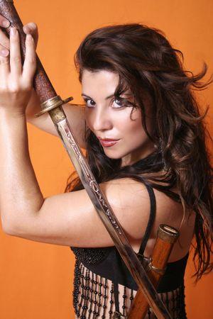 scabbard: Metal Maiden - Brunette la celebraci�n de una espada, con sable sobre el hombro  Foto de archivo