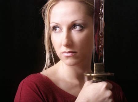 sword fighting: Standing in self Defence...  Soft skin contrasts against cold metal. Stock Photo
