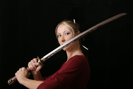 samurai sword: Young female grips a samurai sword, eyes fixed on opponent. Stock Photo