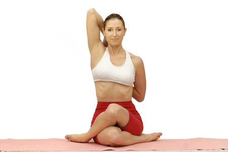 relieve: Woman performing Gomukhasana on a mat. Stock Photo