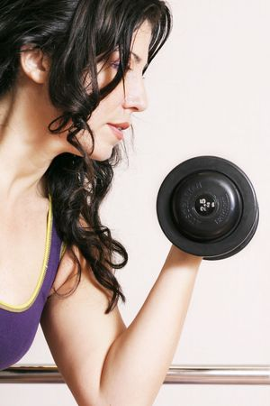 Pump Iron - Weight resistance training. She is holding a 2.5kg (6lb) barbell. Stock Photo