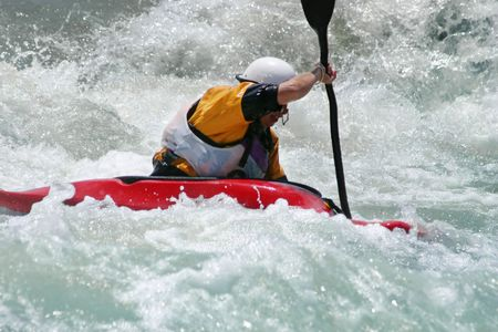 Battling the rapids - extreme action - A kayaker battling strong rapids photo