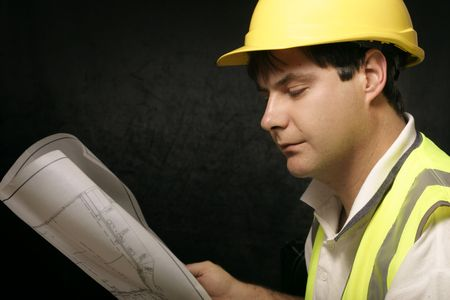 construction draftsman: Workman engineer, miner or builder with architectural plans Stock Photo
