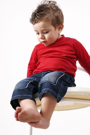 observation: Long Way Down - Toddler sitting  on a high stool makes an observation of his surroundings Stock Photo