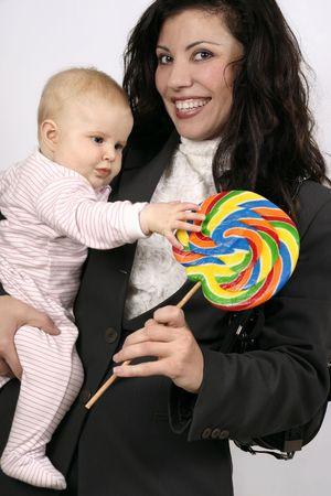 tempting: Smiling working mother holding 5mth old and a tempting candy