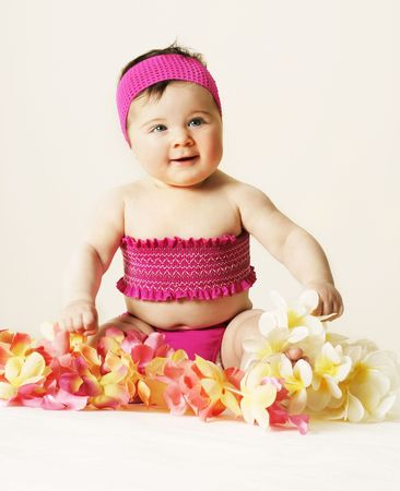 leis: Beachy Baby - Young baby in beach wear and surrounded by floral leis. Stock Photo