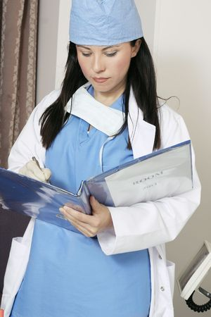Nurse in a ward, recording or updating a patient's records Stock Photo - 263723