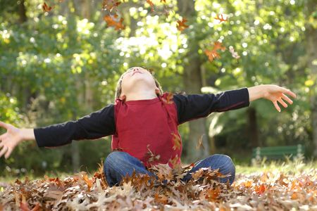 A boy throws fallen leaves up into the air. There is some motion in the hands and falling leaves