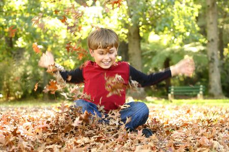 mischievious: Child playing in leaves and laughing gregariouslyVisible motion in arms and especially hands.