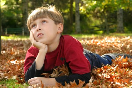 Child resting in a park amongst autumn leaf fall. Stock Photo