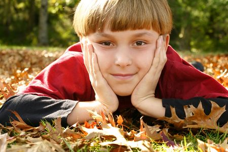 both: A boy laying in a leafy park with his head in both hands and staring ahead. Stock Photo
