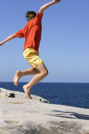 rapture: Leaping - Boy leaps into the air with outstretched arms Stock Photo