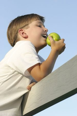 munch: Boy on a fence eating a juicy green apple.Health and nutrition.