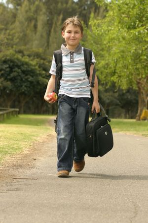 scholastic: Boy walking to school.  He has a backpack, carrying a small portable computer and is holding an apple in his hand Stock Photo