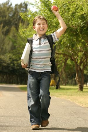 jovial: Back to School - A jovial or enthusiastic child holding a laptop walks to school.
