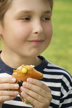 dough nut: Child in a striped shirt eating a sweet dough nut treat.