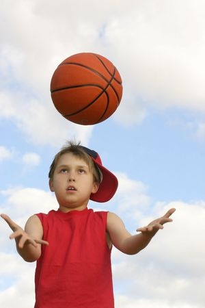 Boy in a red tank top throwing and catching a ball.  Shot against a cloudy sky, afternoon  Focus on face and ball, hands in motion200 iso