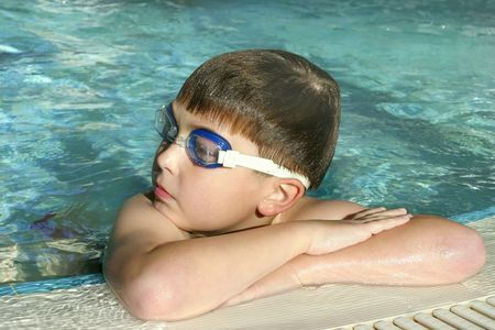 Boy wearing swimming goggles rests poolside Stock Photo