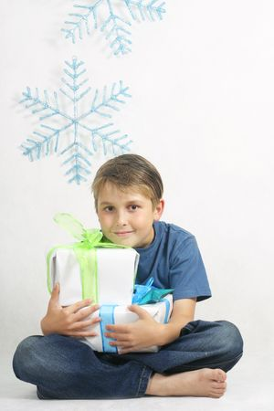 constitutionality: A sitting child holding Christmas gifts tied with bright ribbon.