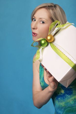 Woman in a dress holding a wrapped gift photo