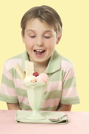delighted: A delighted  boy looks at an ice cream sundae with wafers and cherry on top  placed on a table. Stock Photo