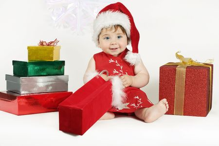 amongst: A baby wearing a pretty red dress and hat sits amongst a colourful array of gifts