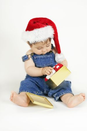 baby open present: Baby girl  in a denim bib and brace and red santa hat opening a gold giftbox