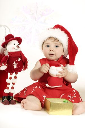 Christmas Play -- 9mth baby in a red dress and santa hat playing with a christmas presents. Stock Photo - 272893