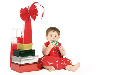 Sweet Delight - Nine month baby wearing a  red dress and sitting amongst gifts and a candy cane  on a white bg. Space for a message too photo