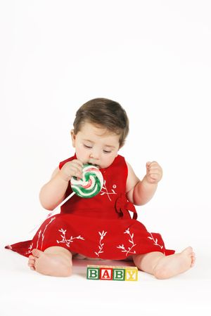 Sweet Candy Girl - Beautiful baby girl sitting, sucking on candy and looking at baby blocks Stock Photo - 273981