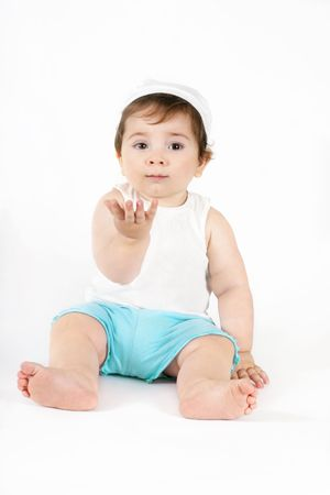 able: Beautiful baby wearing white singlet and blue shorts with her hand outstretched as if holding something imaginary, or you might be able to place a product in her hand. Stock Photo