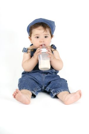 sucking milk: Baby in denim outfit holding a milk bottle Stock Photo
