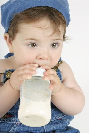 grasping: A young baby grasping a milk bottle