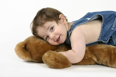 A beautiful baby cuddles a teddy bear