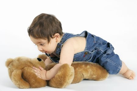 A playful baby crawls on a teddy bear on a white background